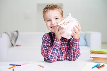 Boy holding his Piggy Bank and smiling cheerfully
