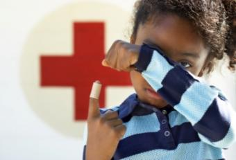 Little boy by Red Cross sign