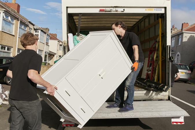men lifting dresser onto van