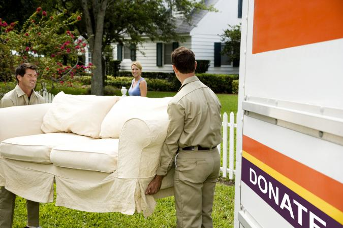 carrying sofa into donation truck