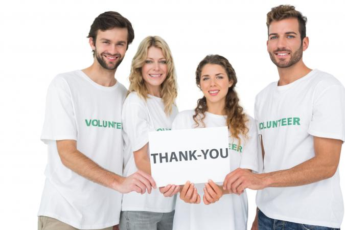 volunteers holding thank you board