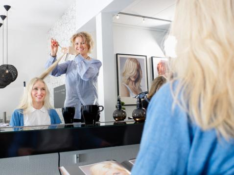 Hairdresser cutting womans hair