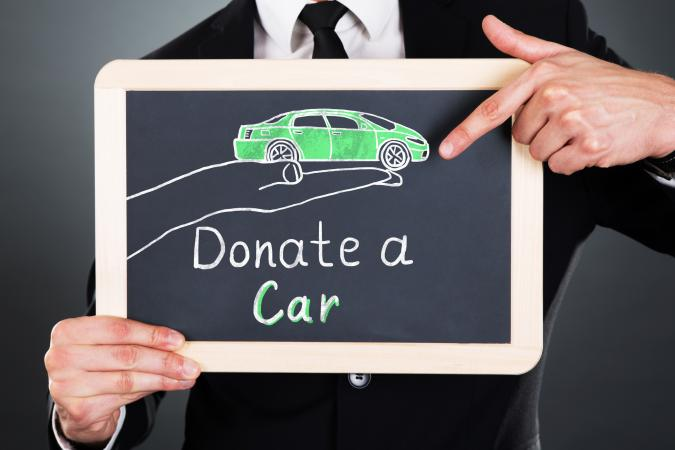 man holding car donation sign