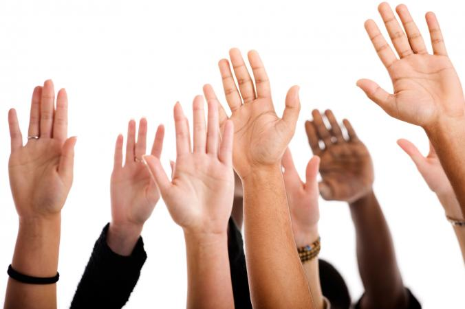 People raising hands to volunteer