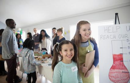 girls standing at fundraising bake sale