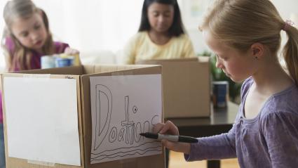 Girl drawing donation sign on cardboard box