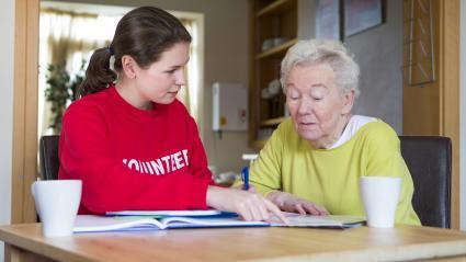 volunteer assisting a senior woman with paperwork