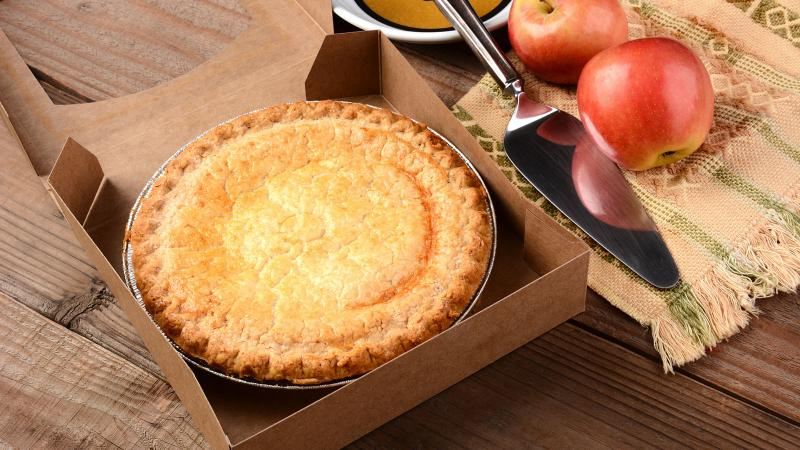 Freshly baked apple pie in a box on a wooden table