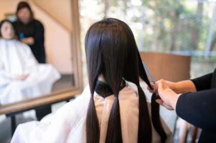 Woman sectioning and cutting hair for donation