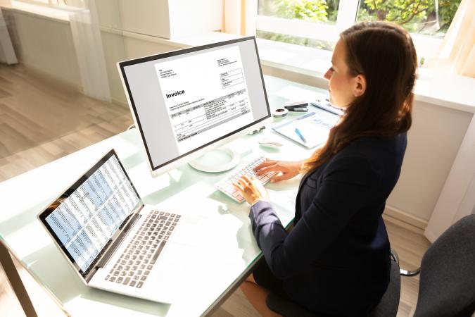 Woman working on invoices on computer