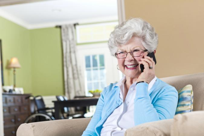 Elderly woman on phone appearing happy