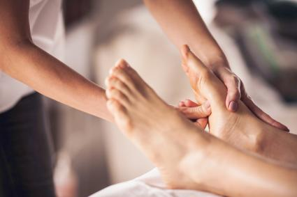 Reflexologist applying pressure to foot