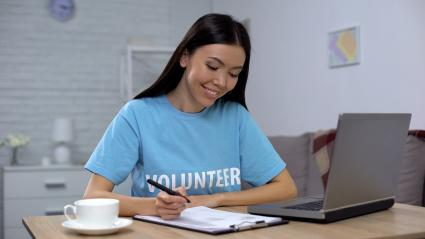 Volunteer working on a laptop taking notes