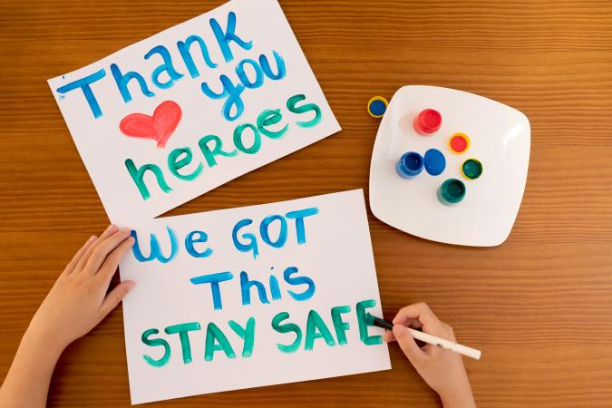 Child writing positive messages to frontline heroes working during Coronavirus (COVID-19) quarantine