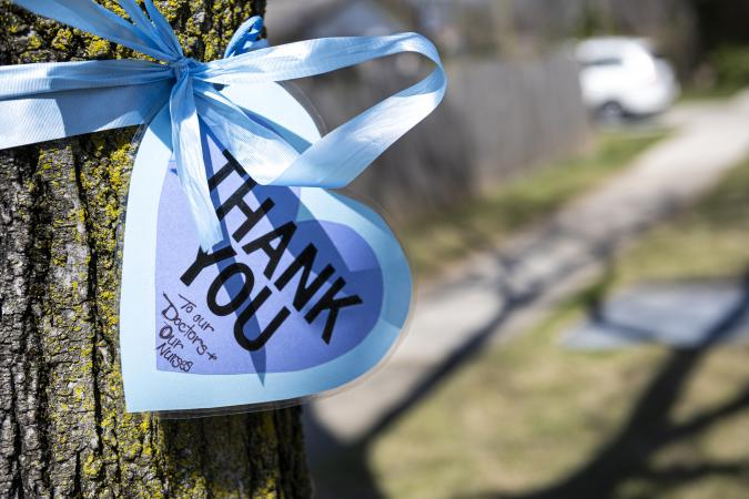 Blue Thank-You sign with blue ribbon wrapped around tree