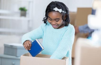 girl packs books in cardboard box