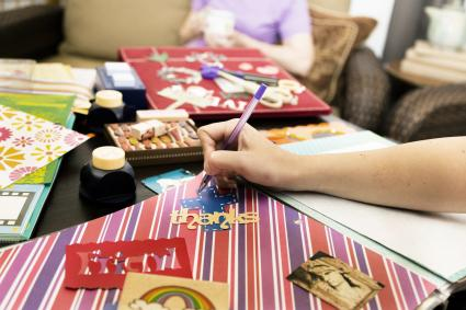 Woman considering arrangements, labels. Scrapbooking