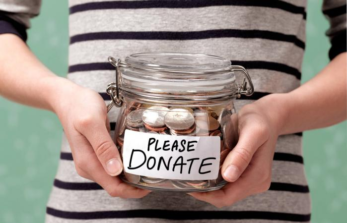 Child holding a charity donation jar