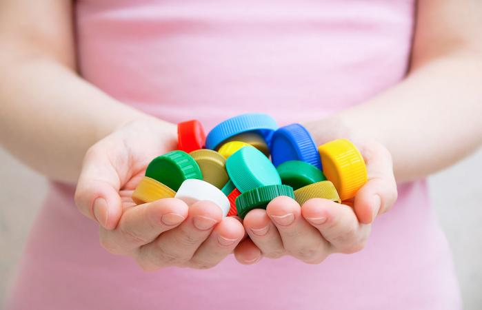 Girl holding plastic bottle caps