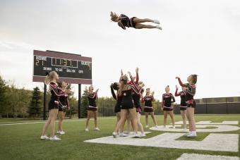 High school cheerleading team practicing on football field