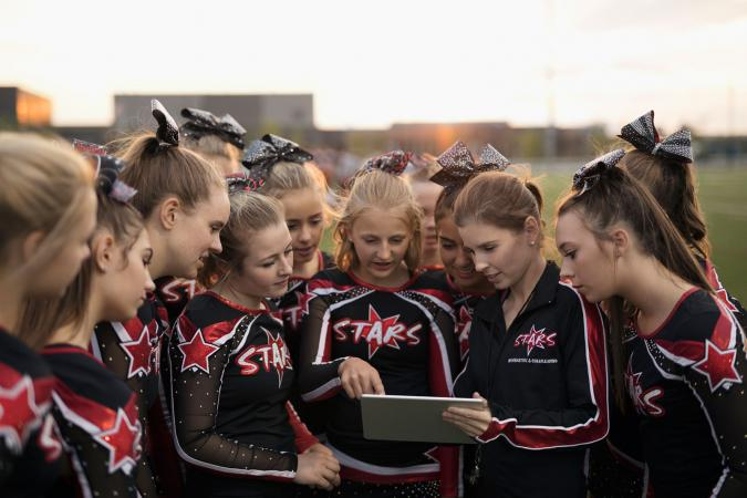 Cheerleading team using digital tablet