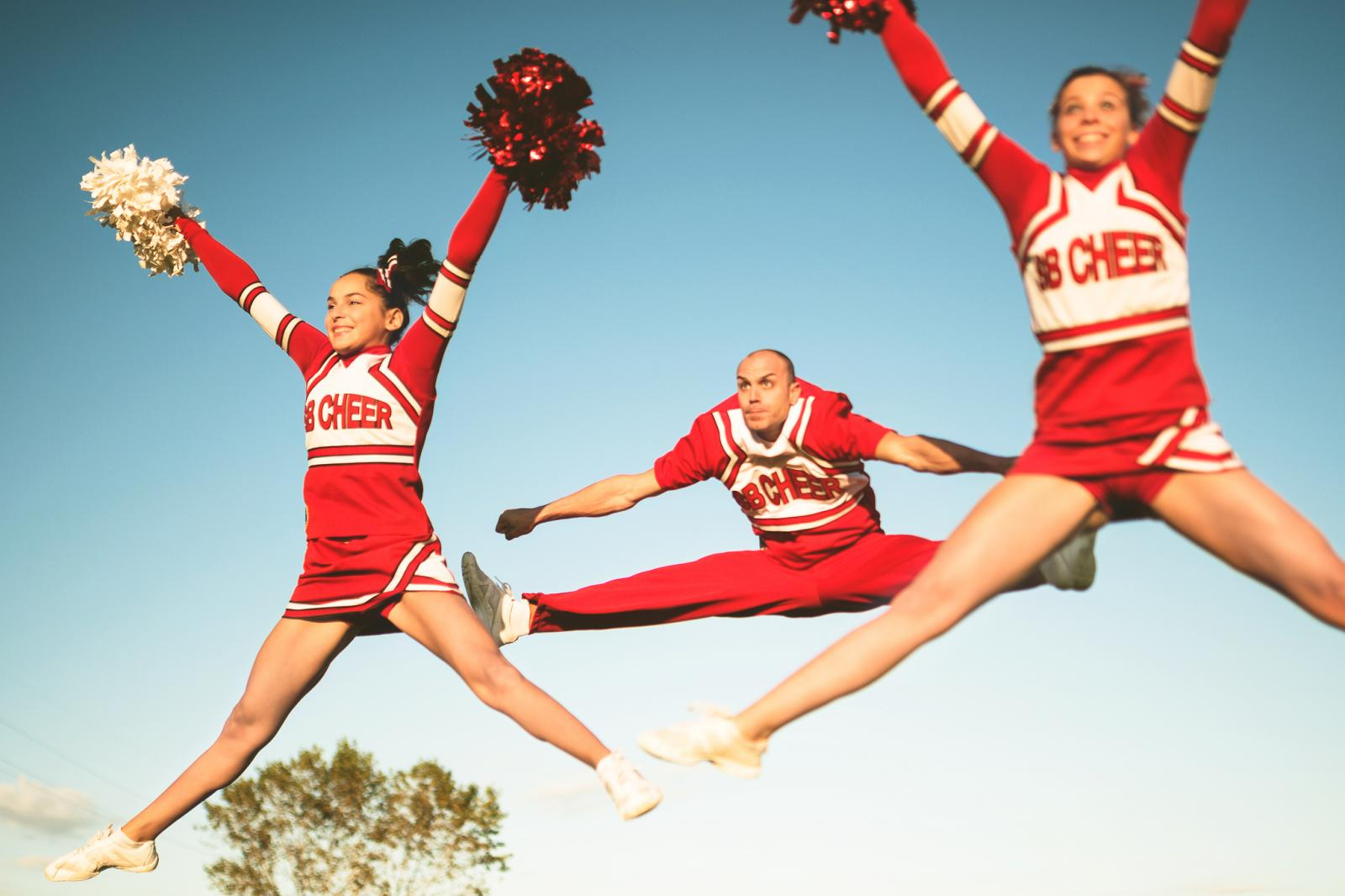 Cheerleaders jumping with pom-poms