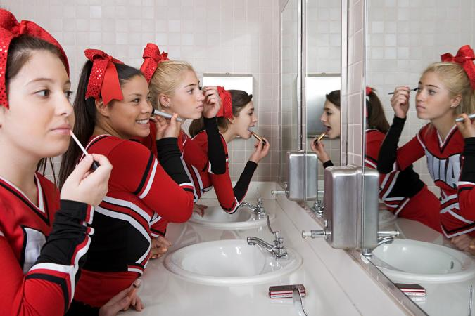 Group of cheerleaders putting on makeup