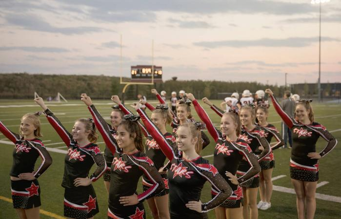 Cheerleaders cheering on football field