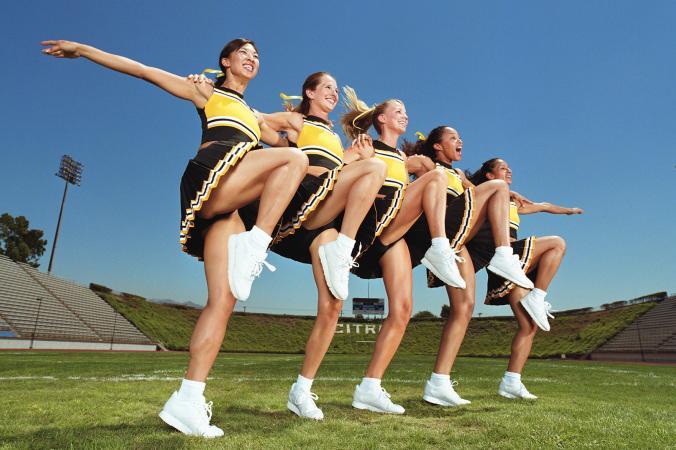 Cheerleaders dancing arm in arm in formation