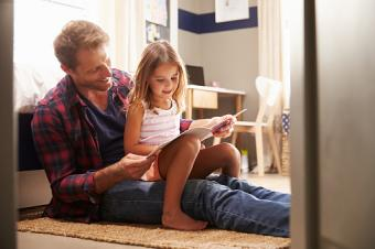 father and young daughter reading
