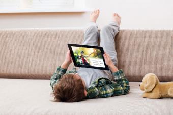 Boy reading on digital tablet