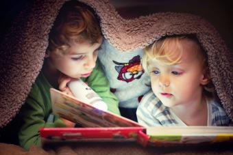 Children Looking in the Book Under the Blanket