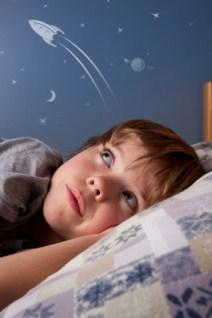 Child in bed, dreaming of space