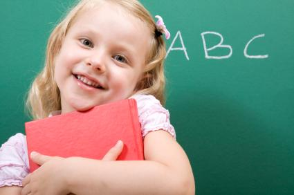 Little girl hugging her alphabet book