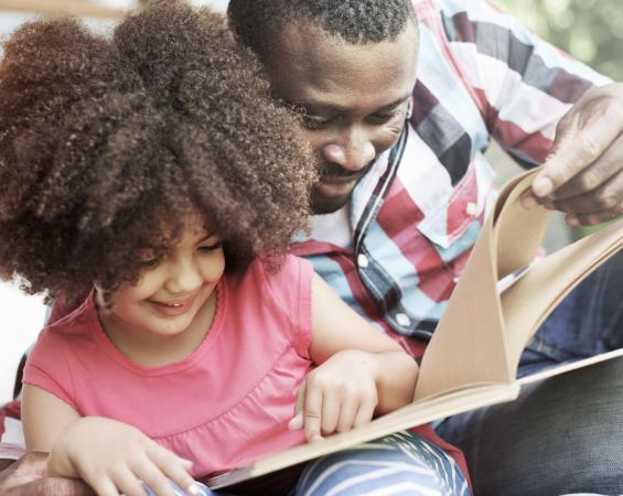 African American father and daughter reading