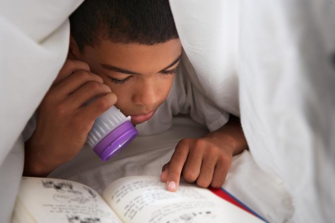 Boy Reading Book Under Blanket