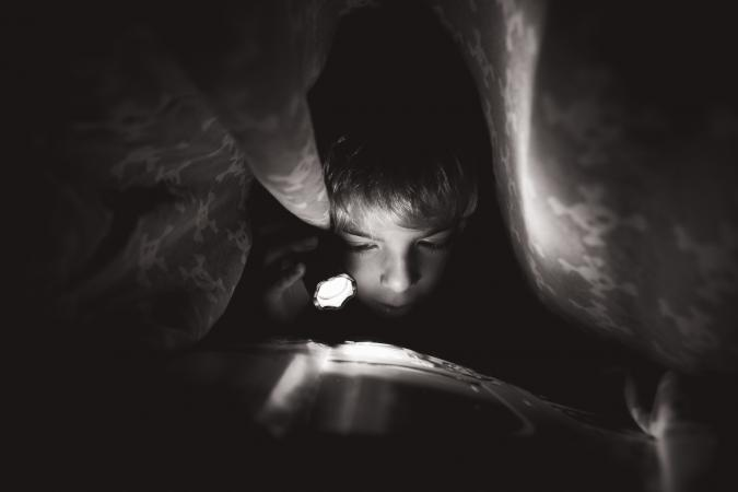 Child reading under the bed sheets