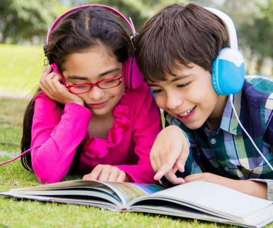 Kids with headphones reading a book