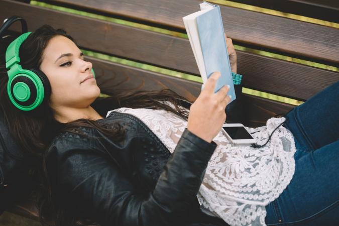 Girl reading book with headphones on