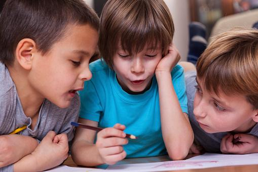 Three children drawing a picture