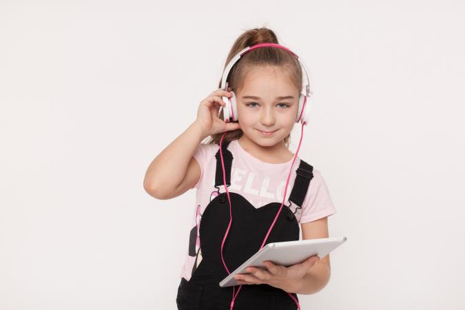 girl with tablet listening to audio book