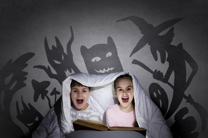 girl and boy reading scary book