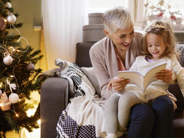 Grandmother and girl reading book while sitting on sofa at Christmas