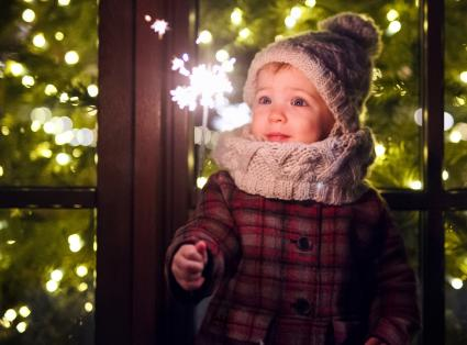 Small girl with sparkler outdoors in winter at night