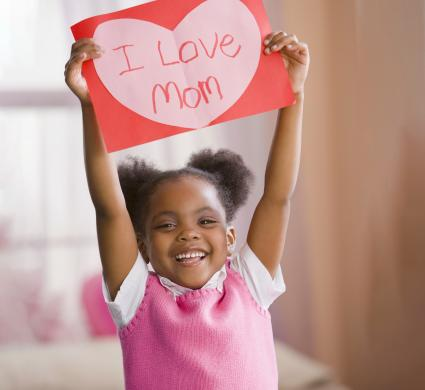 Girl holding up valentine for mother