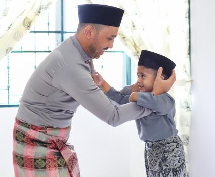 A father helping his son wearing a songkok on Hari Raya Aidilfitri / Eid-Ul-Fitr