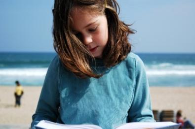 girl reading at beach