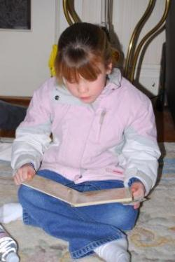 A girl reading in a jacket.