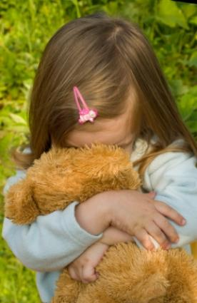 Child clinging to a teddy bear