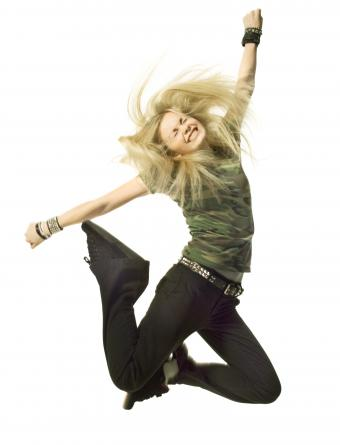 blonde girl in black pants and a camouflage shirt jumps